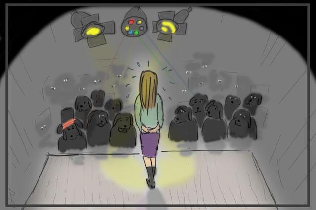 Das Bild zeigt eine Frau, die vor einem Publikum steht