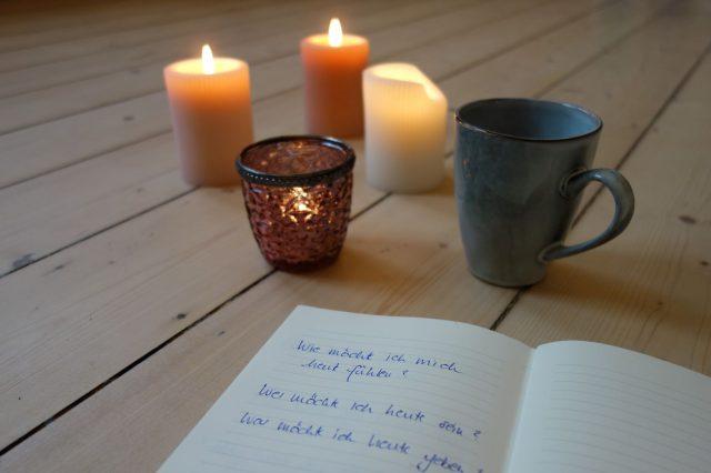 Bild zeigt ein offenes Tagebuch mit Kerzen